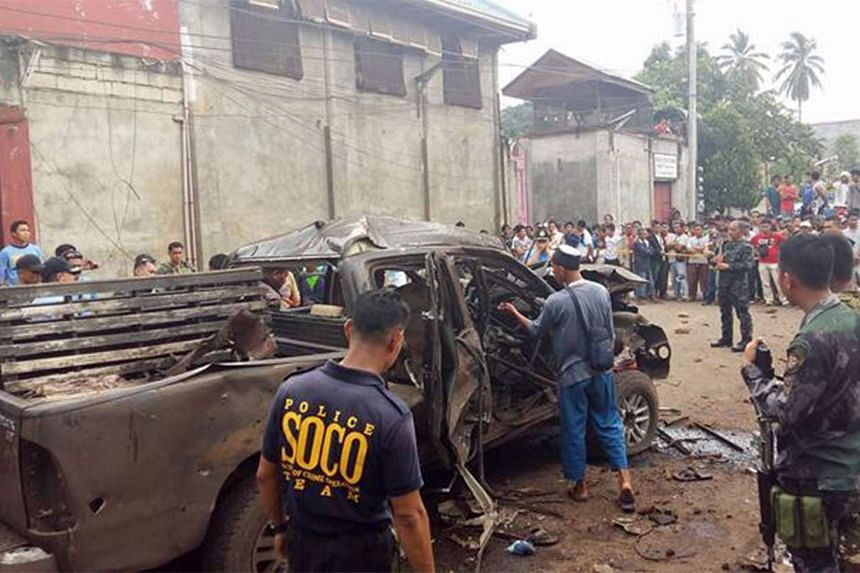 Filipino residents view a damaged vehicle following an explosion in the town of Isabela, Basilan island, southern Philippines, on Oct 1, 2015, At least three were killed and 21 people were injured in a series of bombings in southern Philippines, poli