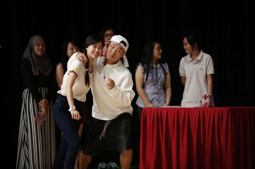 Gary Kang posing with a student on stage at Singapore Polytechnic.