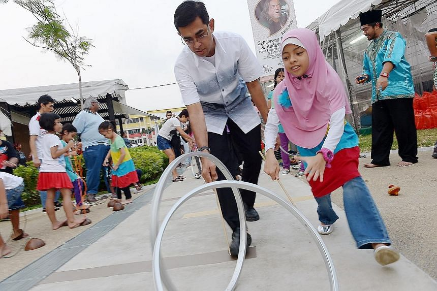 Mr Mohamad Fazlan Abdul Wahab and his daughter Aniis Nurinsyirah trying out a Malay traditional game during an event last month in conjunction with the Malay Language Month.