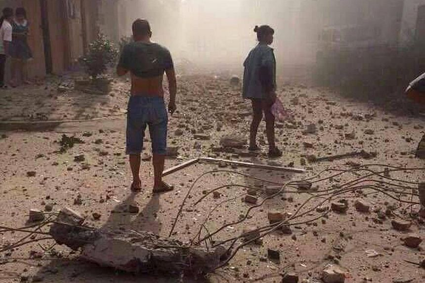 People (right) surveying the aftermath of the explosions that hit Liuzhou city in China's south-western Guangxi region yesterday. A collapsed building (far right) after the blasts yesterday. At least 13 places, including hospitals, shopping malls and