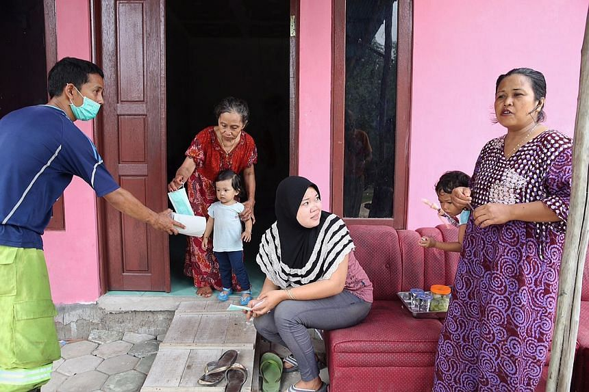 An official giving masks to Kapuas regency residents (from left) Mastika, her granddaughter Mutiara Lestari, neighbour Masita and her daughter Amelia Putri, and Mutiara's mother Mahrita.