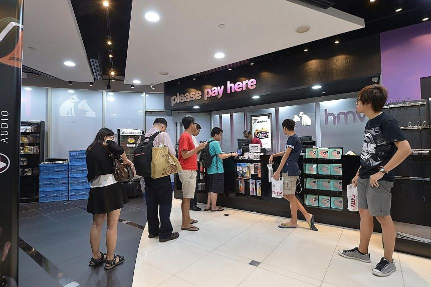 The last few customers queuing to pay for their purchases last night at the HMV store in Marina Square before it closed its doors for good.