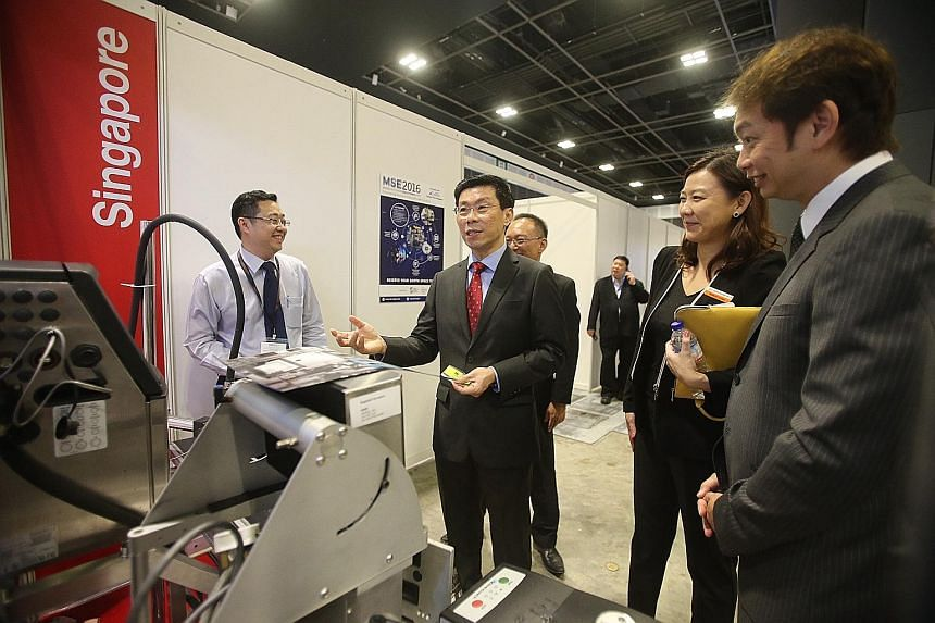 Mr Lee Yi Shyan (centre) at the Manufacturing Solutions Expo 2015 held at the Suntec Convention Centre yesterday. He spent his last day as Senior Minister of State for Trade and Industry and National Development shuttling between industry events, inc