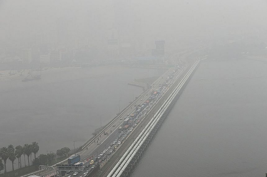 The Causeway, seen yesterday in photos taken at 7am (top), when the three-hour Pollutant Standards Index (PSI) was at 125, and at 3pm (above), when the reading was at 203. The 24-hour PSI stayed within the unhealthy range of 101 to 200 yesterday. The