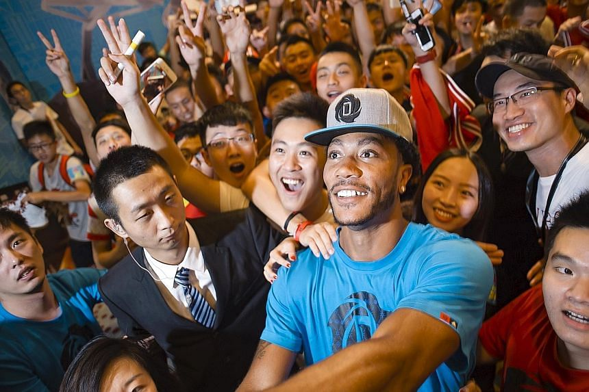 The Chicago Bulls' Derrick Rose posing for a wefie with Chinese fans during a publicity event in Guangzhou in August. His NBA team have not put a date on the injury-prone guard's return.