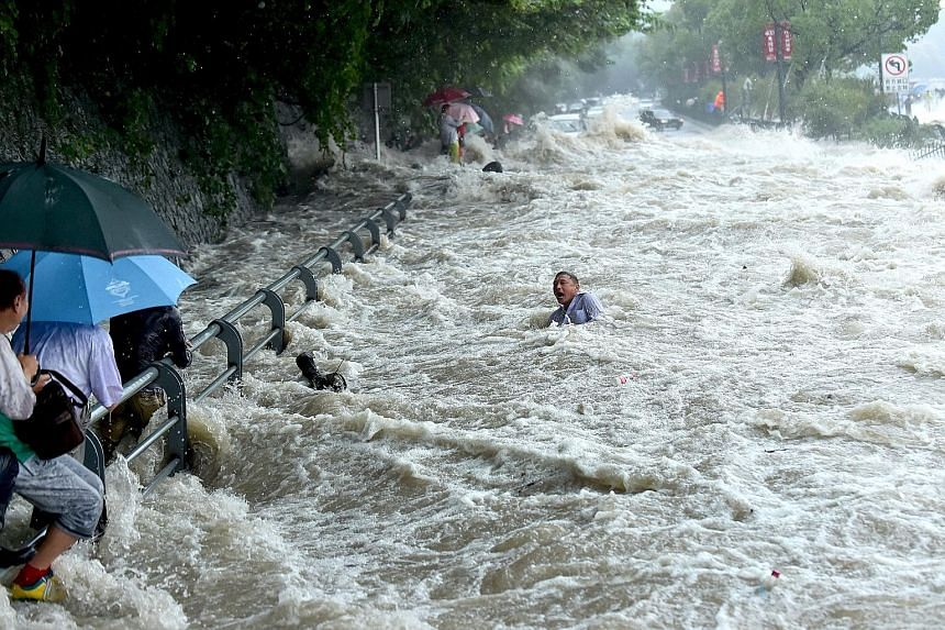 A tourist struggling in the water, before he managed to stand up and wade away, after a wave strengthened by the influence of Typhoon Dujuan hit a river bank in Hangzhou, in eastern China's Zhejiang province, on Tuesday. Spectators watching the tides