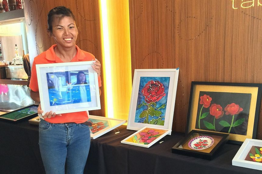 Ms Ng Xiu Zhen, who has cerebral palsy, will have her works displayed alongside those of four others in a travelling exhibition that was unveiled at W Singapore hotel in Sentosa Cove on Sunday. Displayed works at the Art on the Move exhibition are on
