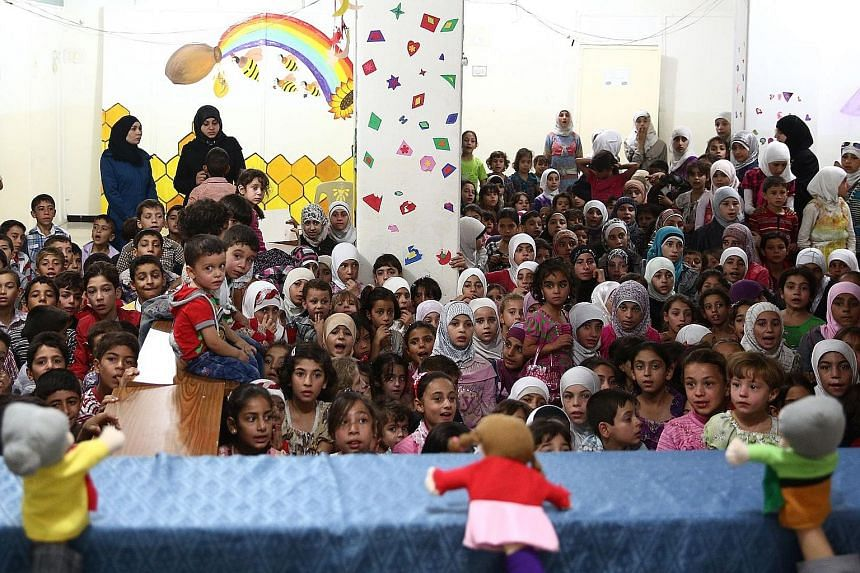 Syrian children who have lost one or both of their parents in the conflict watching a puppet show during a party organised by an NGO in the rebel-held district of Douma, east of Damascus, on Monday. Douma is part of the rebel-held Eastern Ghouta area