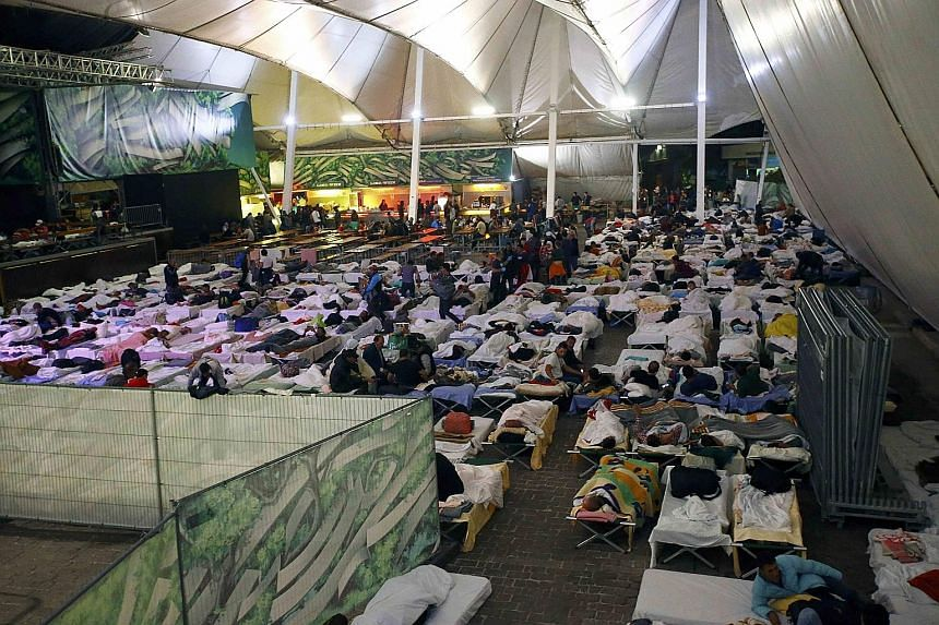 Migrants resting on camp beds at an improvised shelter in a concert hall in Wiesen, Austria.