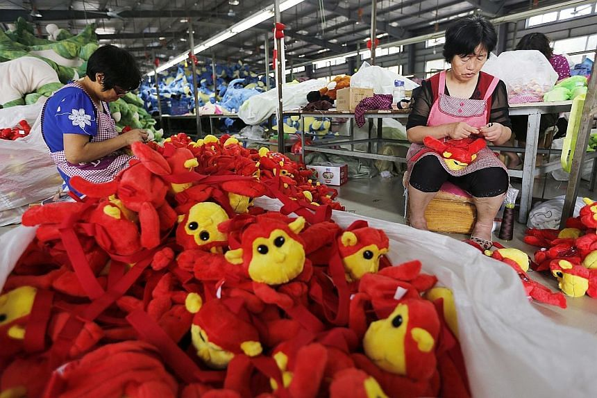 Chinese workers putting the finishing touches on toys in a factory before packing them for export. The Chinese slowdown caused WTO to cut this year's forecast for growth in Asian imports and exports.