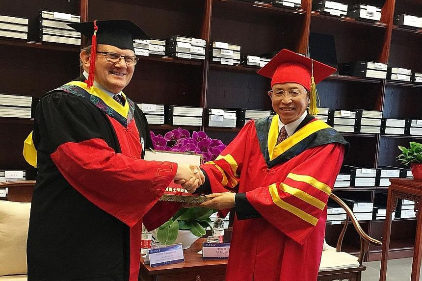 NTU president Bertil Andersson receiving his honorary doctoral degree from Tianjin University President Li Jiajun yesterday in recognition of his contributions in academia and forging international partnerships.
