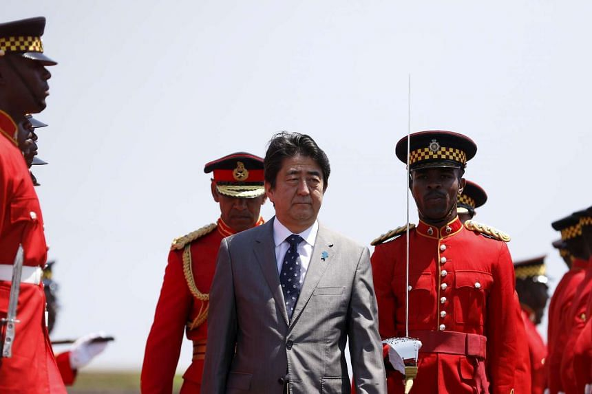 Japanese Prime Minister Shinzo Abe (centre) reviews an honour guard after his arrival in Kingston, Jamaica on Sep 30, 2015.