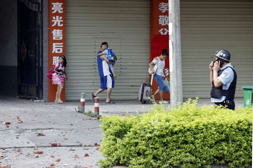 Residents are evacuated from the area of a damaged building a day after a series of blasts in Liucheng county in Liuzhou, south China's Guangxi province on Oct 1, 2015.