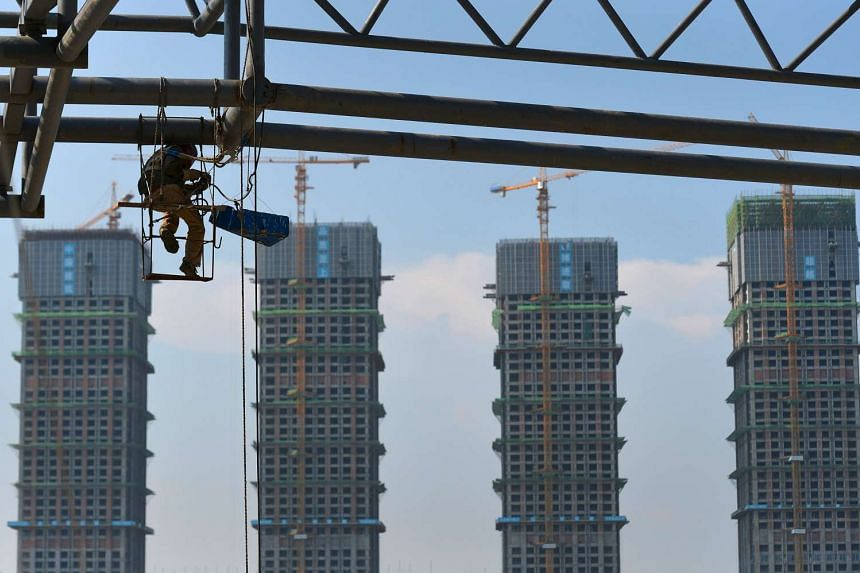 A labourer working at a construction site of an amusement park next to new property buildings in Hefei, Anhui province.