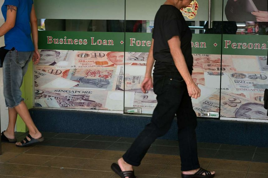 People walking pass a moneylending shop in Toa Payoh Central on Nov 4, 2014.
