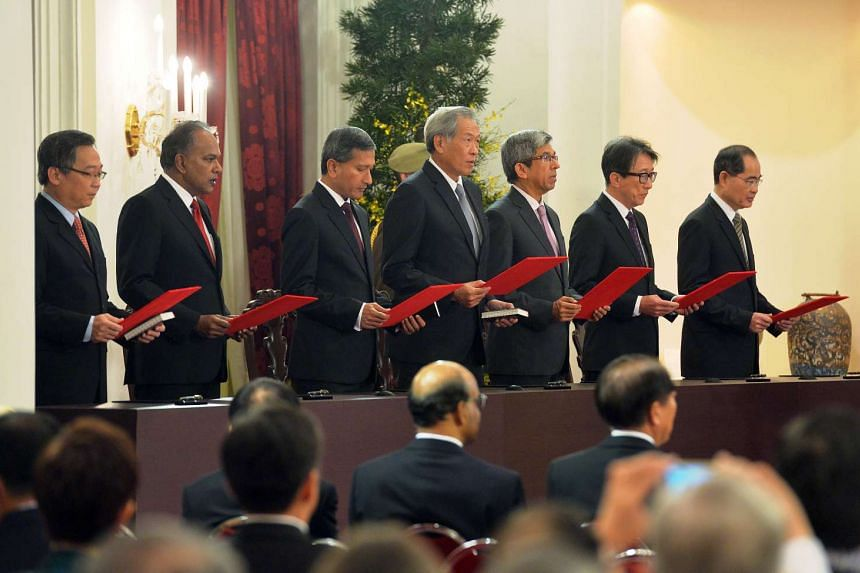 Cabinet ministers taking their oaths during the swearing-in ceremony at the Istana.