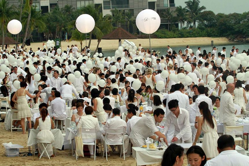About 3,000 diners in Singapore tucking into their meals at the Diner En Blanc picnic in the evening of July 5, 2014. This year's event is being postponed because of the haze.
