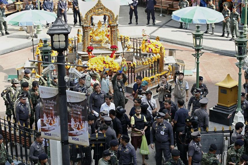 Thai police officers escort a suspect identified as Adem Karadag (in yellow) during a crime re-enactment at the bomb blast site at Erawan Shrine in Bangkok on Sept 26, 2015.