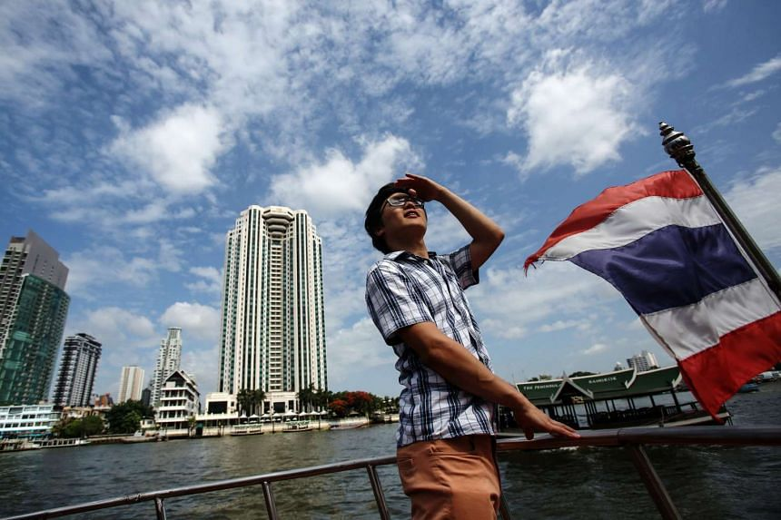 A tourist from South Korea stands on the deck of a tourist boat on the Chao Phraya river as it navigates past the Peninsula Hotel in Bangkok, Thailand on Saturday, June 28, 2014.