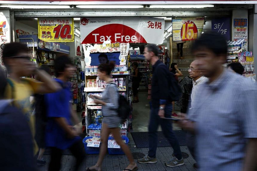 Pedestrians walking past a sign advertising tax-free shopping in Tokyo on  Sept 28, 2015.
