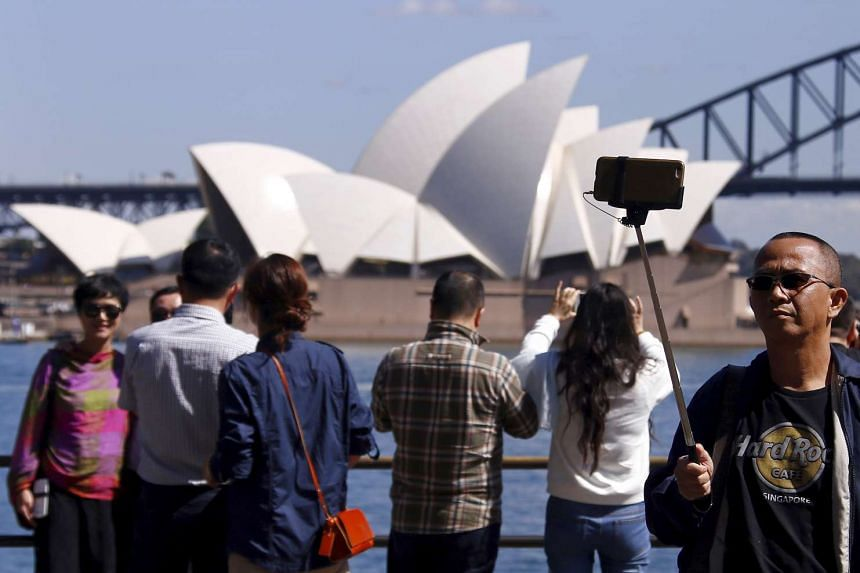 Chinese tourists take pictures of themselves standing in front of the Sydney Opera House in Sydney, Australia on Sept 28, 2015.