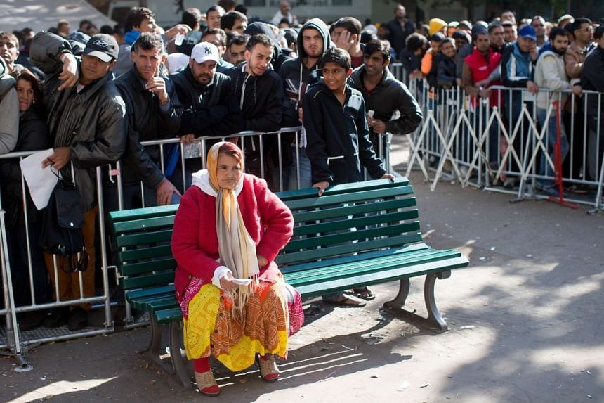 Migrants wait for their registration outside the State Office of Health and Social Affairs (LAGeSo) in Berlin on Oct 1, 2015.