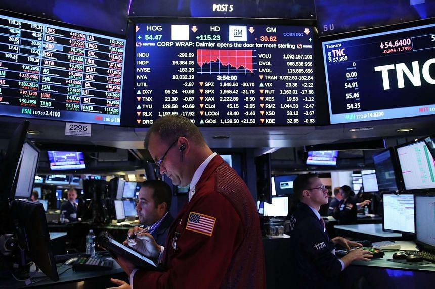 Traders work on the floor of the New York Stock Exchange (NYSE). U.S. stocks fluctuated on Thursday morning, following the Standard & Poor's 500 Index's best gain in three weeks, as investors remain cautious following equities' worst quarter since 20