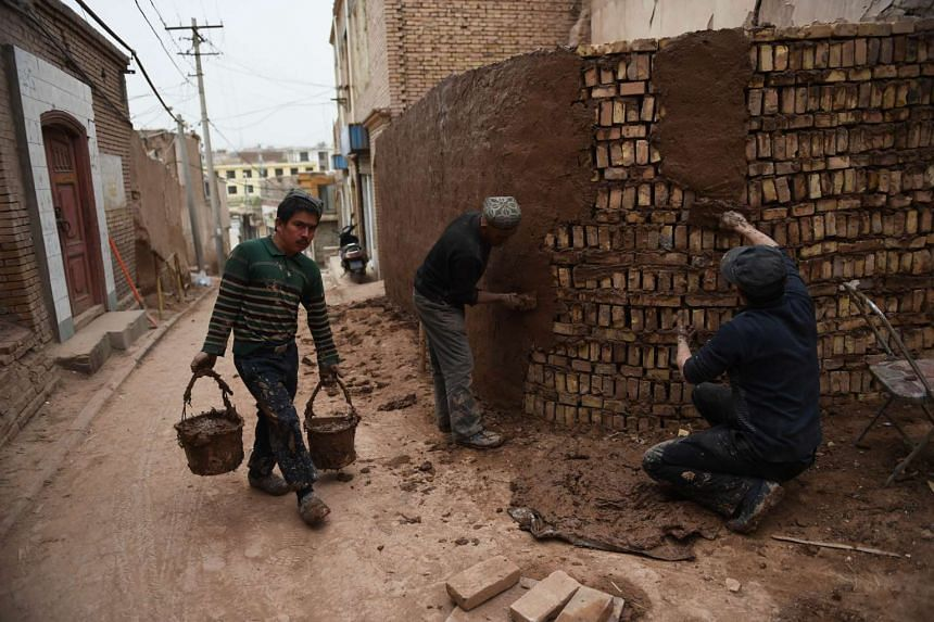 Workers using modern bricks and mud-based cement to repair a wall in the old city in Kashgar, in China's western Xinjiang region on Apr 19, 2015.