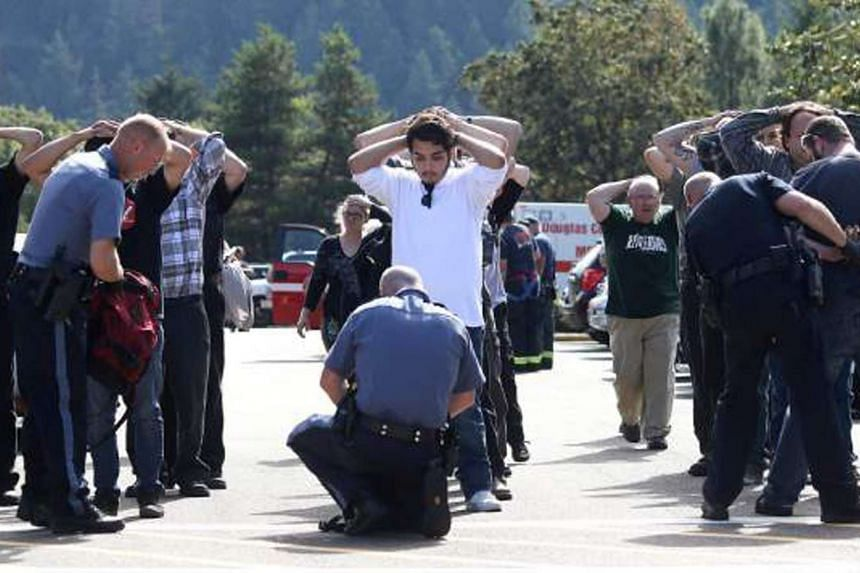 Police officers inspecting bags as students and staff are evacuated from the campus following a shooting incident at Umpqua Community College in Roseburg, Oregon, on  Oct 1, 2015.