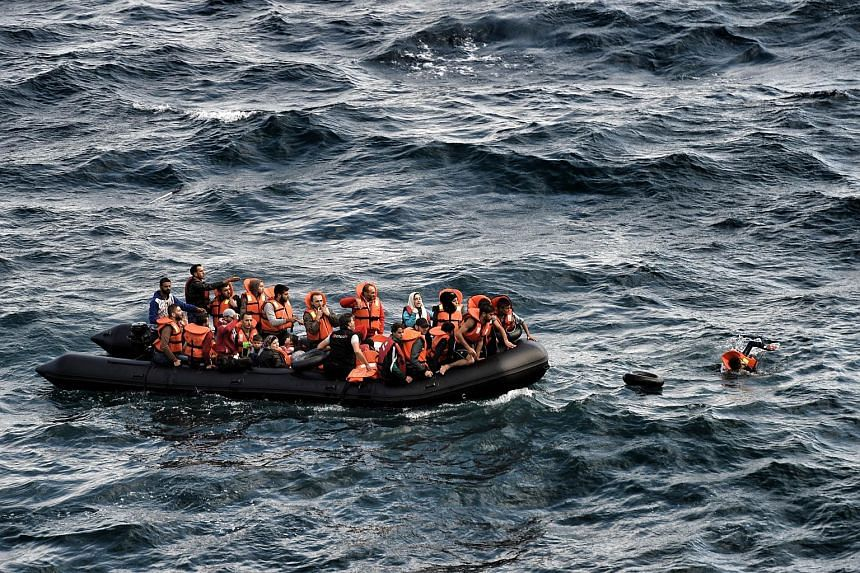 Refugees and migrants arriving on a dinghy to the Greek island of Lesbos after crossing the Aegean sea from Turkey on Sept 30, 2015.