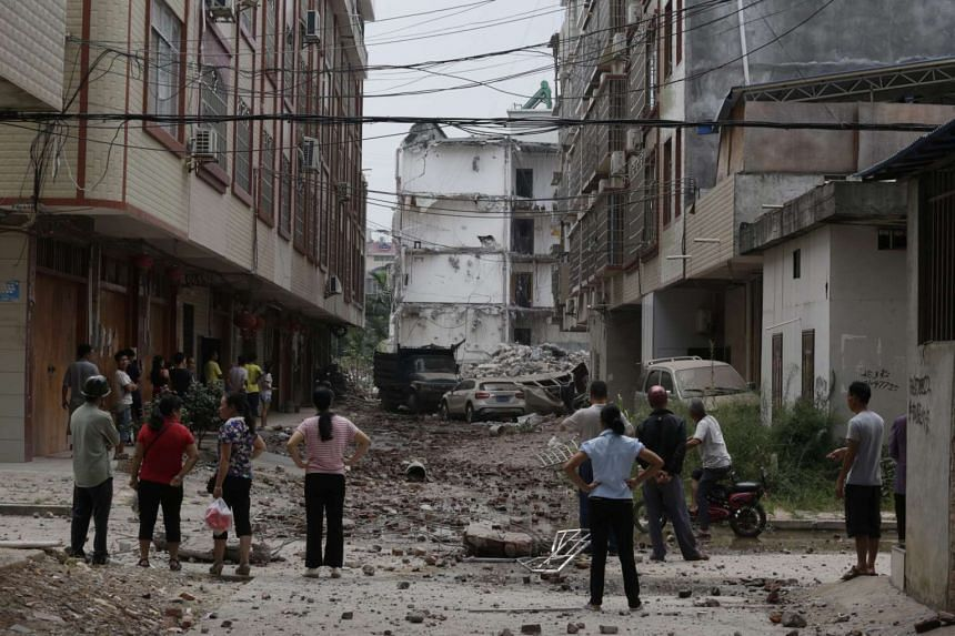 Local residents looking at damaged vehicles and to the street near by a partially collapsed residential building after an explosion reportedly caused by explosives hidden in parcels, in Liucheng county, Guangxi Zhuang autonomous region, China, on Oc