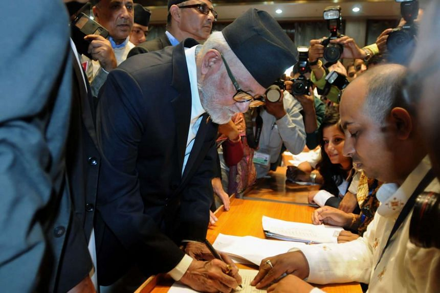 A file picture taken on Sept 18, 2015 shows Nepalese Prime Minister Sushil Koirala signing a final copy of the newly passed constitution at the parliament in Kathmandu. Koirala on October 2 said he would ask Nepal's president to begin the process of
