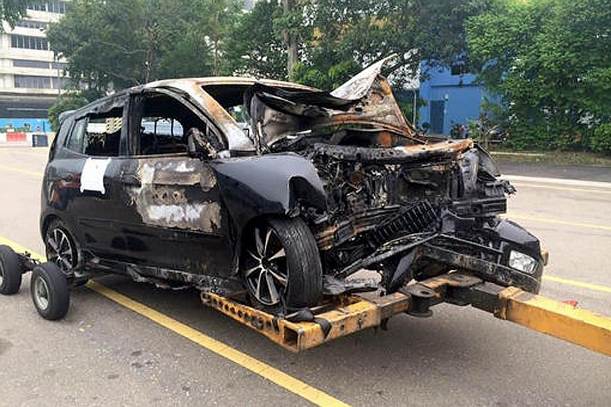 Cabby Weng Dianlai (left) rushed to the aid of Mr Raymond Ang, whose car (above) had crashed into a tree in Marymount Road and burst into flames on Sept 24.