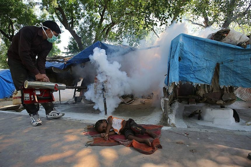 An Indian Municipal Corporation sanitation worker fumigating an area in Old Delhi yesterday, even as a child slept on the ground nearby. The anti-dengue fumigation drive to curb breeding sites for mosquitoes comes amid a dengue outbreak in New Delhi.