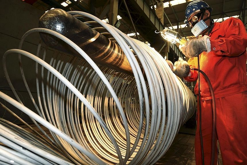 A worker polishing steel coils at a factory in Dalian, Liaoning province, China. Surveys of China's factory and services sectors showed the world's second-largest economy may be cooling more rapidly than earlier thought, with deeper job cuts.
