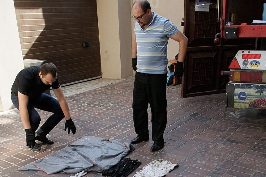 Investigators from the self-proclaimed Donetsk People's Republic inspecting clothes of passengers who died in last year's Malaysia Airlines Flight MH17 crash in Donetsk, Ukraine, on Wednesday. The clothes and pieces of the wreckage will be sent to th