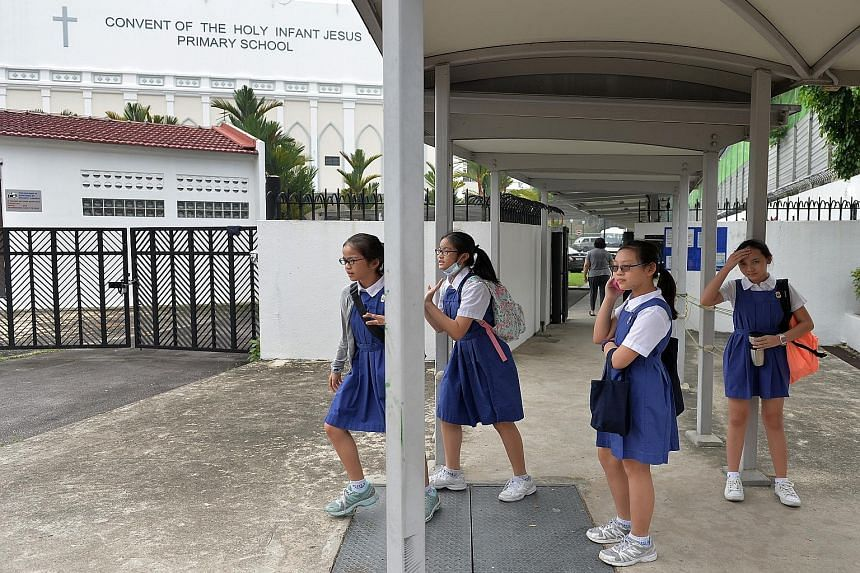 Primary 6 pupils from CHIJ Primary (Toa Payoh) leaving the school compound after their PSLE exam yesterday. Some 40,000 pupils took their first PSLE paper yesterday morning, many of them in air-conditioned halls and classrooms with air purifiers as t