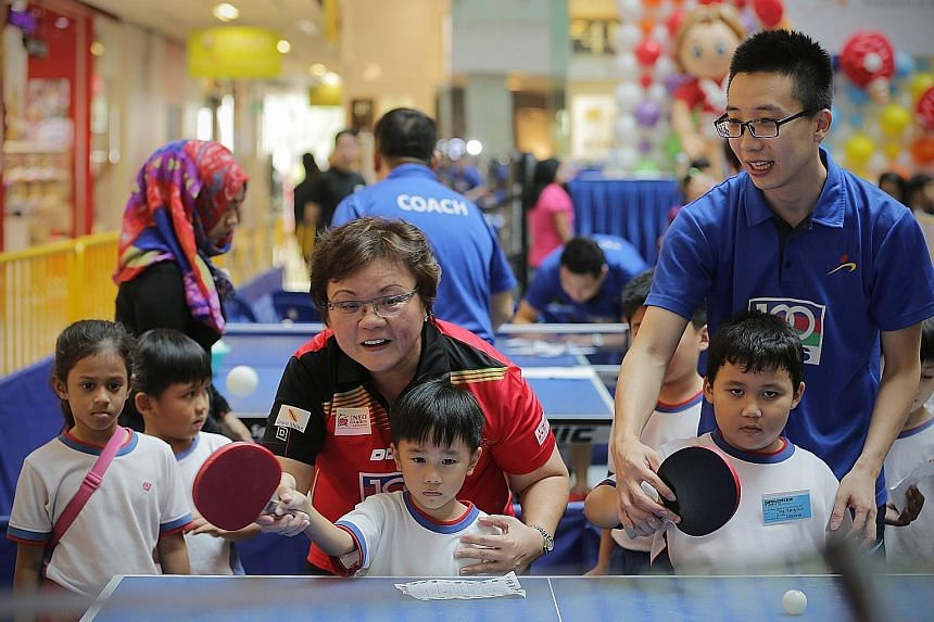 Singapore Table Tennis Association (STTA) president Ellen Lee teaching the game to a group of pre-school children at the STTA-PAP Community Foundation Table Tennis Carnival yesterday. National paddlers Li Hu and Zhou Yihan were also present at the ev