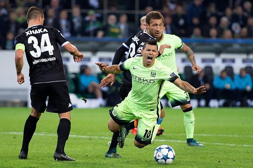 Manchester City striker Sergio Aguero (centre) tumbling in the penalty box under a challenge by Borussia Moenchengladbach's Fabian Johnson in the final minute of the match in Germany. The Argentinian then coolly slotted home the penalty kick to win t