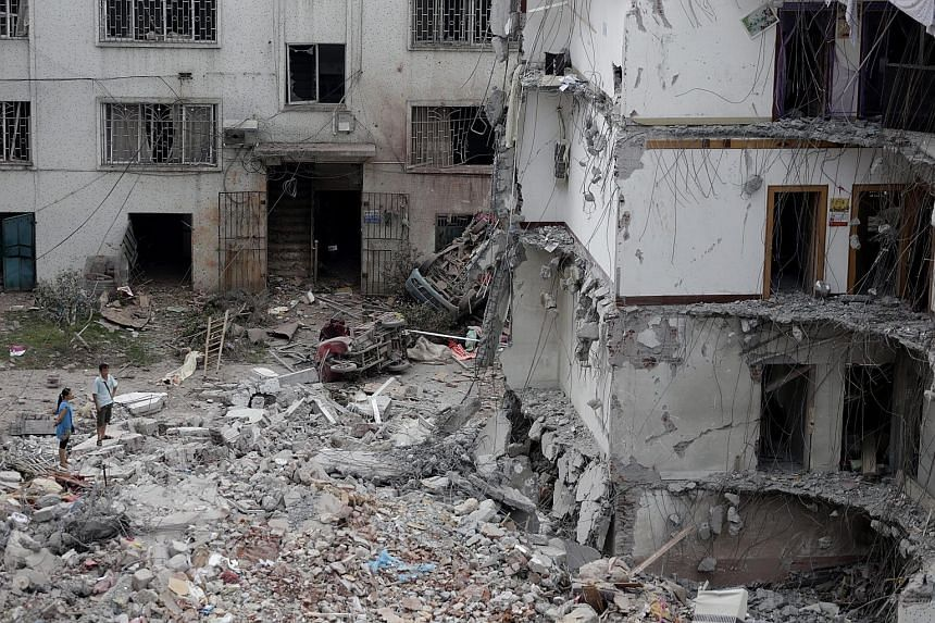 Residents standing near a partially collapsed residential building after a blast, reportedly caused by explosives hidden in parcels, in Liucheng county, in Liuzhou, yesterday.
