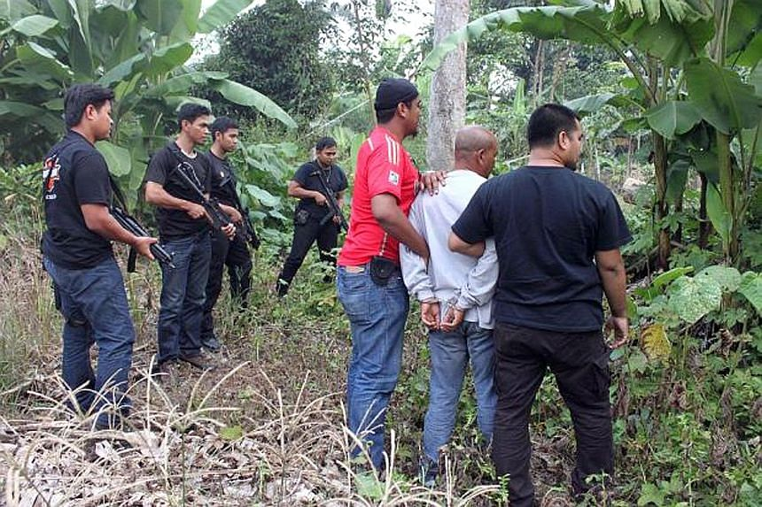 Police detaining a paramilitary member in Perak's Kuala Kangsar town for suspected involvement in a militant group linked to ISIS. There are now some 100 fighters from Malaysia and 500 from Indonesia with ISIS, many of them part of its Malay Archipel