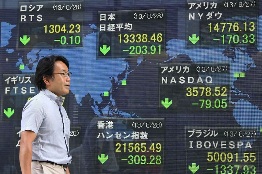 A pedestrian walking past an electronic monitor displaying stock indices outside a securities firm in Tokyo, Japan.
