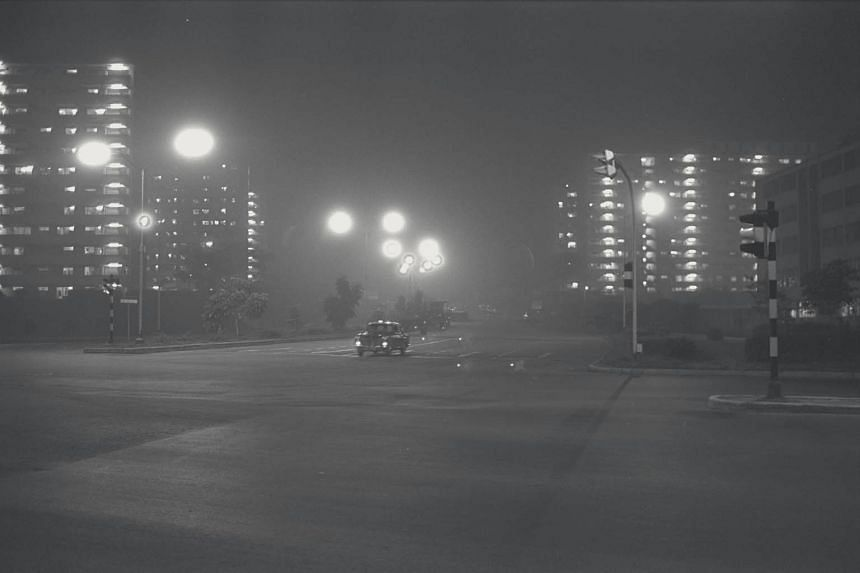 A car driving with full headlights on a brightly-lit street due to the thick haze on the evening of Oct 13, 1972.