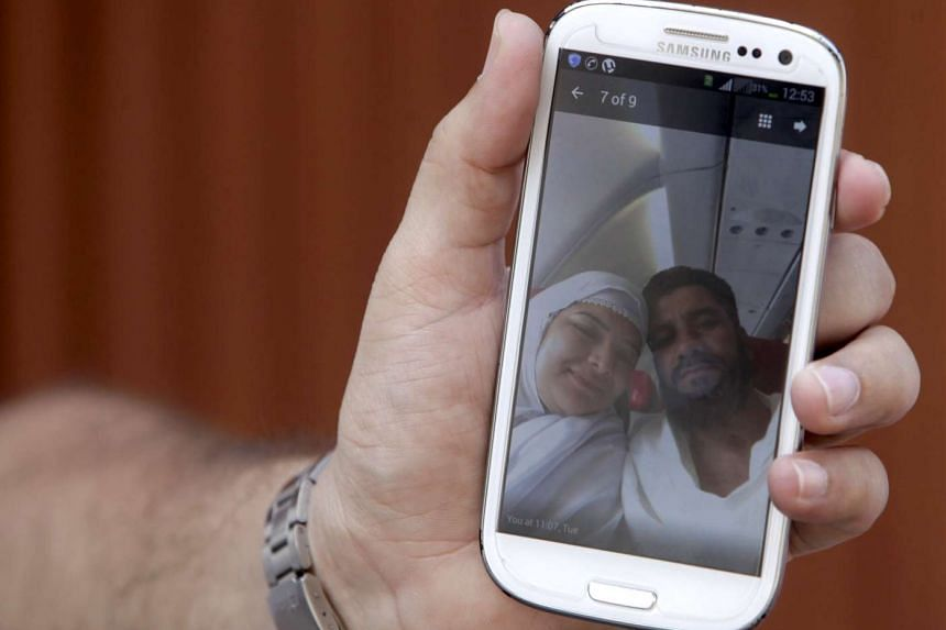 A man from Pakistan shows a photo of his missing sister on Sept 30, 2015. Her husband (right) was confirmed killed in the haj stampede.