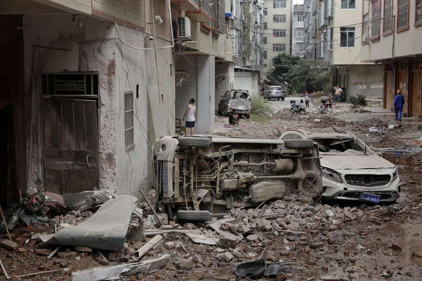 Damaged vehicles and residential buildings seen after an explosion reportedly caused by explosives hidden in parcels, in China, on Oct 1 2015.