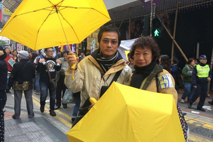 Teacher Terence Yeung and his wife Ambo Yeung joined pro-democracy protesters holding yellow umbrellas, symbols of the Occupy Central movement, during the march in the streets to demand universal suffrage in Hong Kong on Feb 1, 2015.