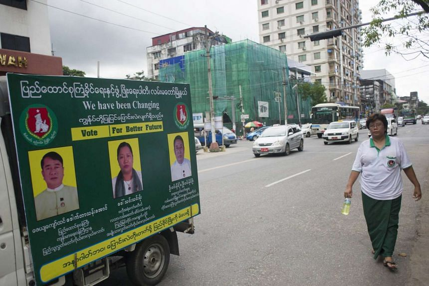 A Union Solidarity and Development Party (USDP) member walking down a road with a campaign van ahead of the upcoming general election, in Yangon on Oct 1, 2015.