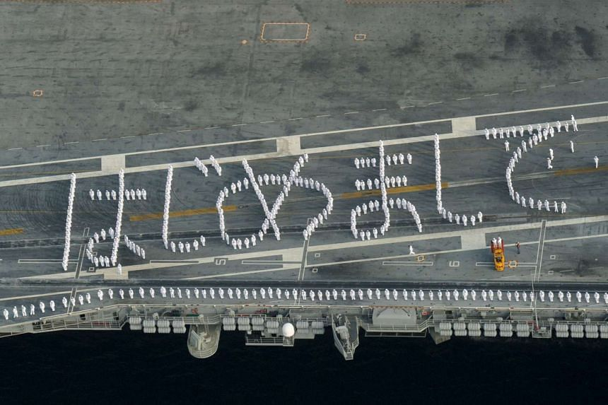 US sailors on the deck of the USS Ronald Reagan, a Nimitz-class nuclear-powered supercarrier, forming Japanese words loosely translated into English as ''nice to meet you''. The carrier arrived at the US naval base in Yokosuka, south of Tokyo, yester