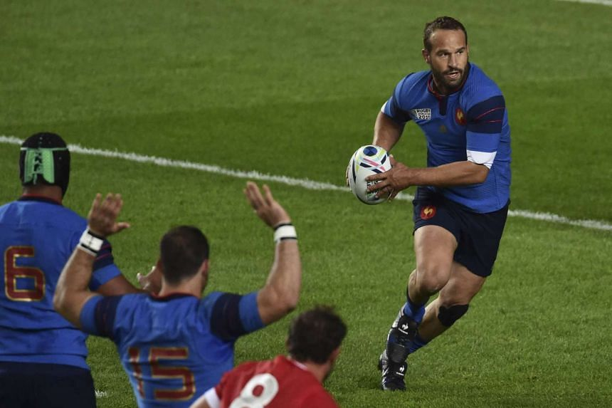 France's fly half Frederic Michalak (right) runs with the ball.