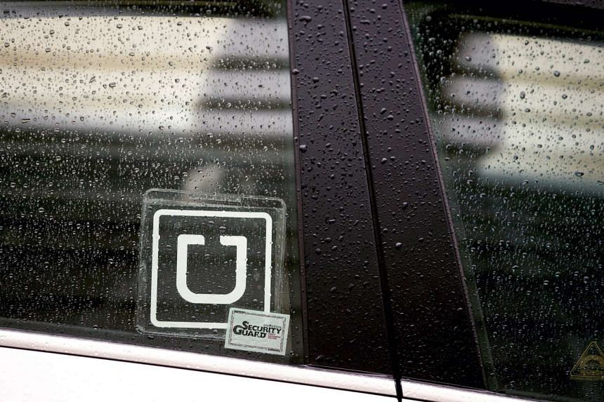 An Uber logo is displayed on the window of a vehicle. The Singapore Government will be reviewing private car-sharing apps such as Uber.